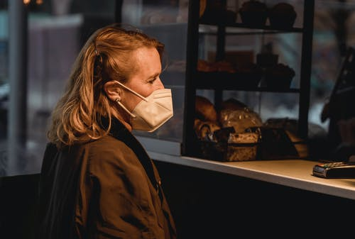 Customer in respiratory mask against bakery counter