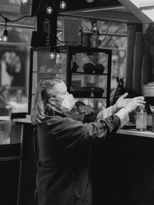 Black and white side view of elderly female customer in protective mask applying antibacterial gel at counter in bakery