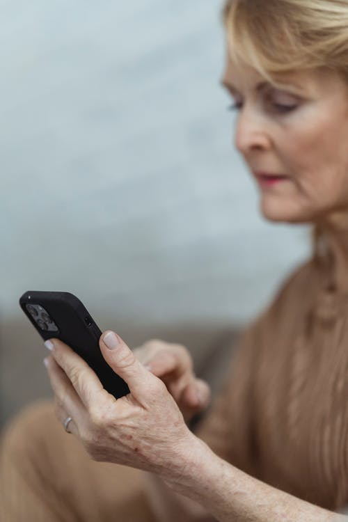 Crop senior woman chatting on smartphone at home