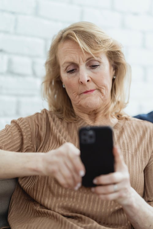 Pensive elderly female with wrinkled face skin chatting on mobile phone against brick wall in house room