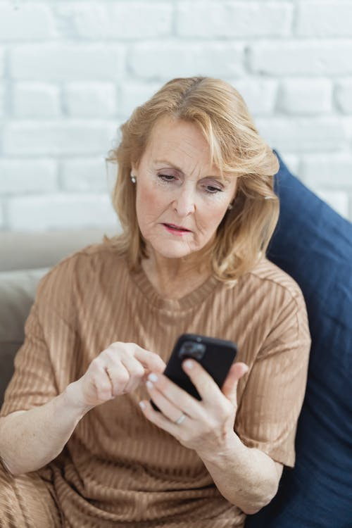 Elderly woman chatting on smartphone on sofa at home