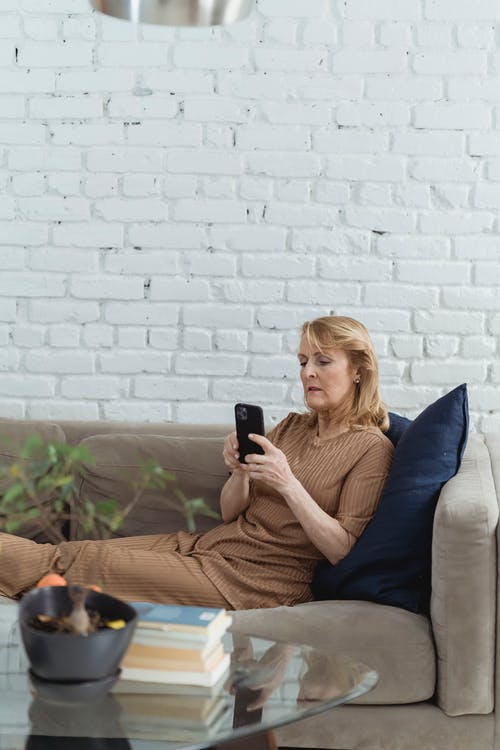 Elderly female surfing internet on mobile phone while resting on couch against table with books in loft style house