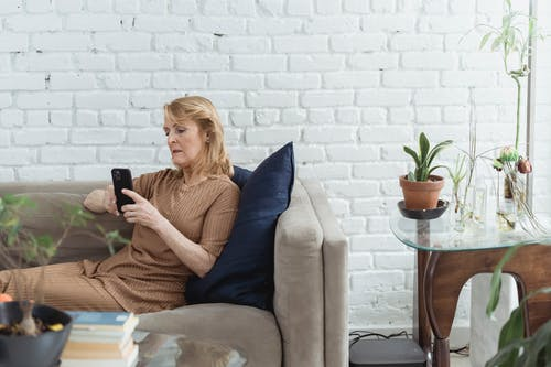 Elderly woman chatting on smartphone on sofa in living room
