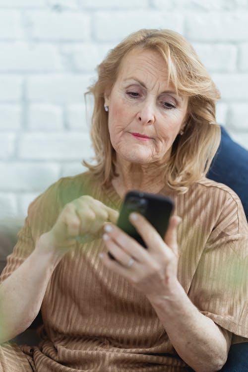 Elderly woman surfing internet on smartphone in room