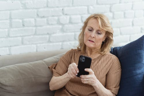 Senior female surfing internet on mobile phone while sitting on sofa against brick wall at home