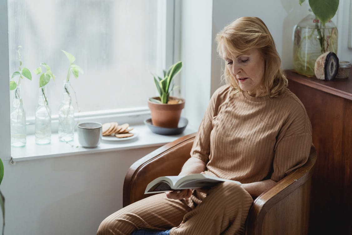Elderly woman reading textbook against tea and cookies in house