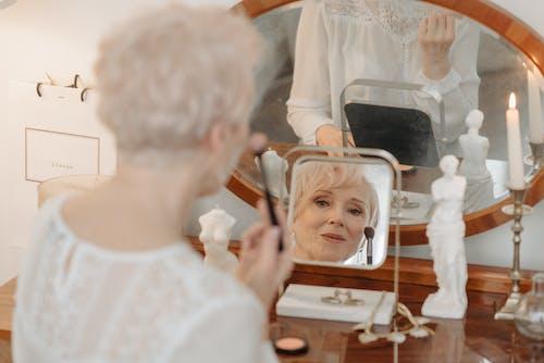 An Elderly Woman Applying Blush On Makeup