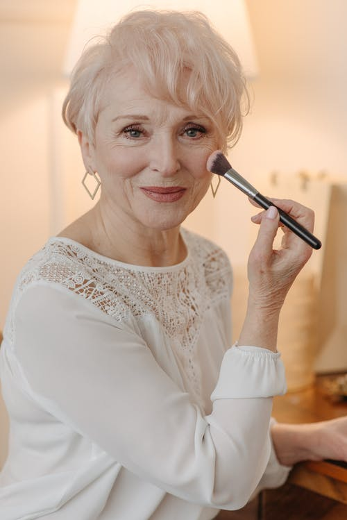 An Elderly Woman in White Dress Applying Makeup