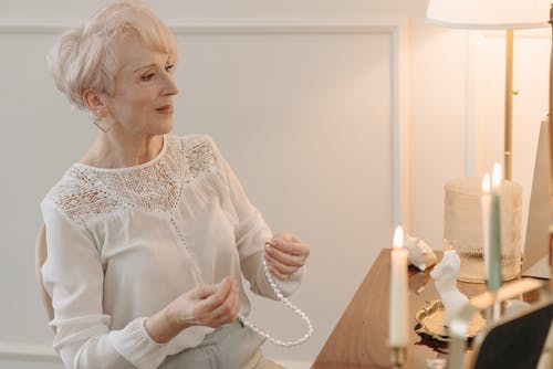 A Woman About to Wear a Pearl Necklace