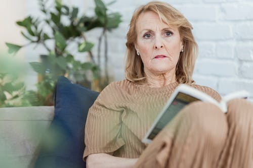 Serious elderly woman sitting on couch with book and looking away thoughtfully