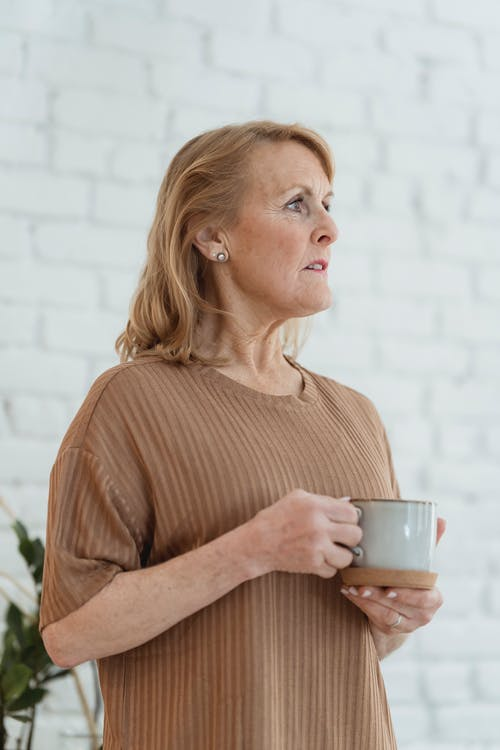 Dreamy senior woman drinking coffee and looking away at home