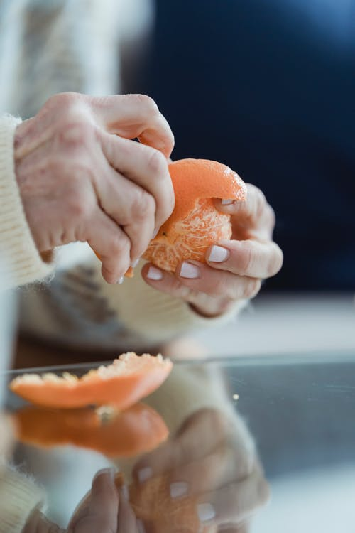 Crop anonymous mature female in sweater peeling mandarin while sitting at table with mirrored top at home