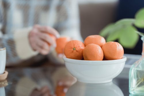 Bowl with fresh tangerines served on table near crop unrecognizable woman