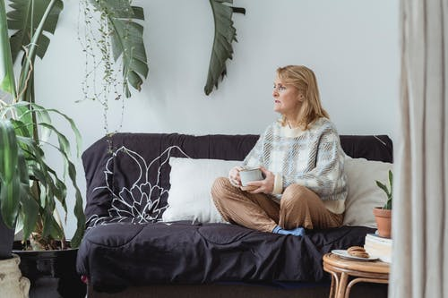 Full body of peaceful middle aged woman with blond hair in casual clothes drinking coffee and looking away thoughtfully while resting on sofa with crossed legs