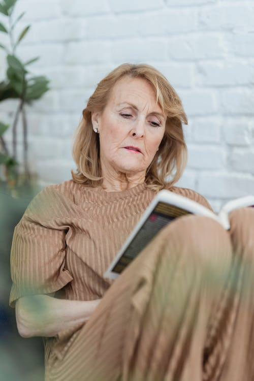 Concentrated elderly woman reading interesting novel at home