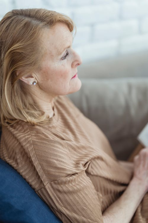 Side view of tranquil mature woman with blond hair sitting on comfy sofa with opened book on knees and looking away dreamily