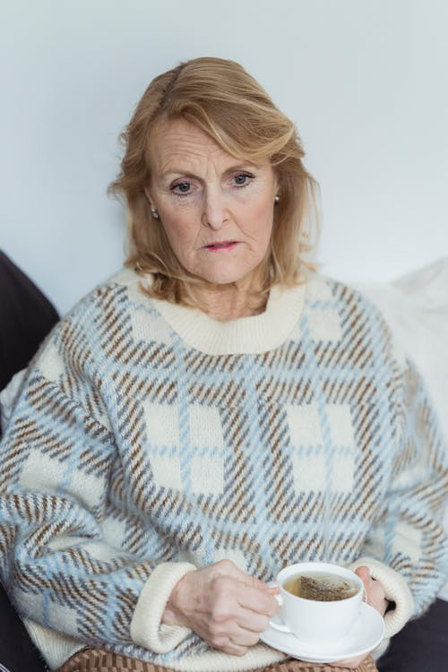Melancholic elderly woman drinking cup of tea on couch and looking away