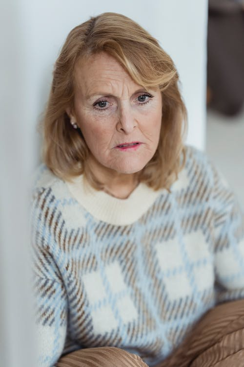 Sad middle aged woman leaning on wall and looking away thoughtfully