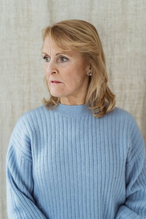 Serious young middle aged lady with blond hair in stylish blue sweater standing near curtains and looking away thoughtfully