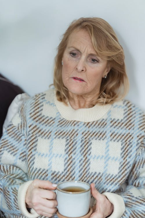 Lonely middle aged woman with blond hair in warm casual clothes looking away sadly while resting on sofa with cup of hot tea