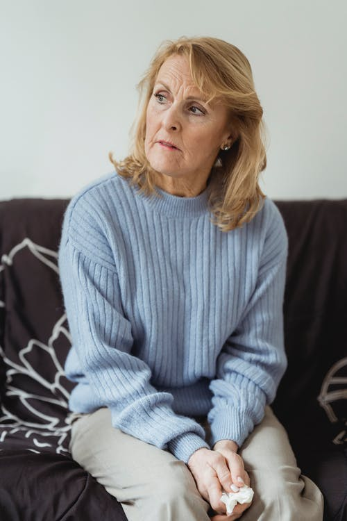 Lonely mature woman looking away sadly sitting on sofa