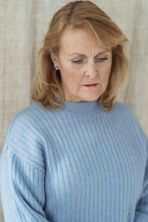Melancholic mature woman looking down sadly