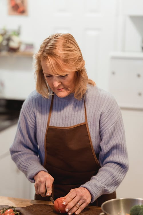 Concentrated middle aged lady in casual clothes and apron standing near counter while using knife to cut tomato on cutting board in light kitchen near metal bowl