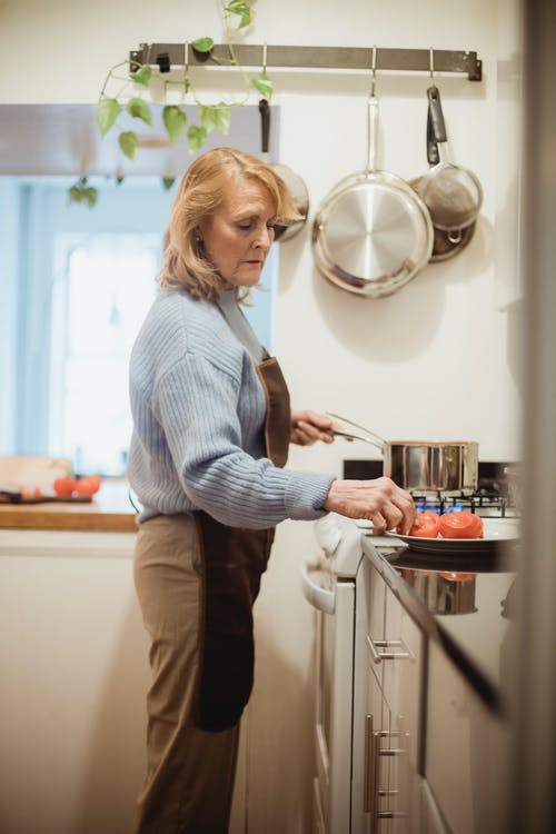 Woman in Blue and White Stripe Long Sleeve Shirt and Brown Pants Standing in Kitchen
