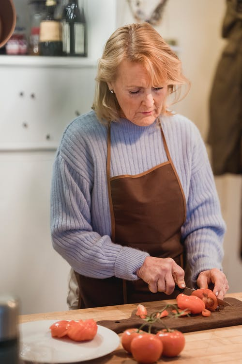 Focused mature female chef in apron cutting fresh ripe tomatoes on chopping board while cooking in kitchen