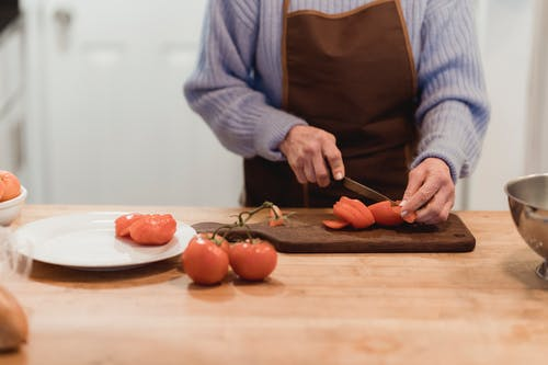 Crop faceless housewife cutting ripe tomatoes in kitchen