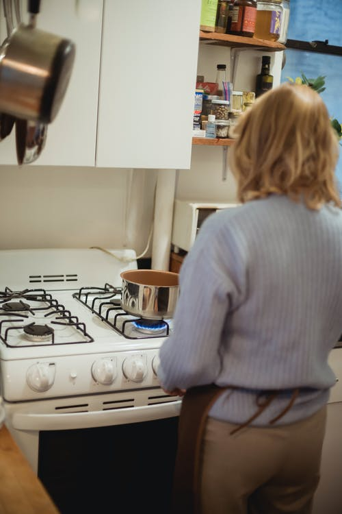 Back view unrecognizable female in apron standing near saucepan placed on stove in kitchen