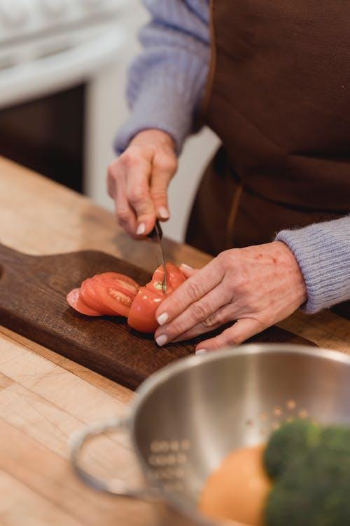 Crop faceless housewife cutting ripe tomato