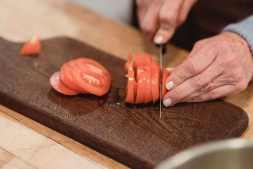 Crop anonymous female chef with manicured hands slicing organic ripe tomato on wooden board while cooking