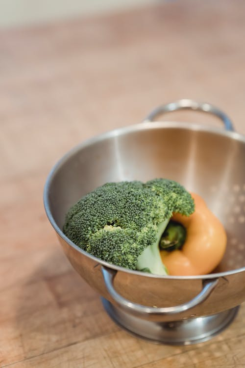 Raw ripe broccoli and yellow capsicum placed in steel colander on wooden table in kitchen