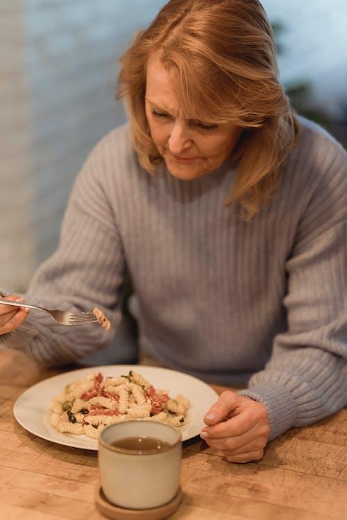 Crop mature female enjoying delicious tomato pasta
