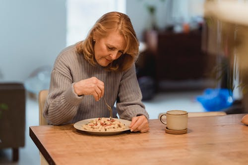 Emotionless senior female wearing blue sweater enjoying yummy vegetable pasta while sitting at table in living room
