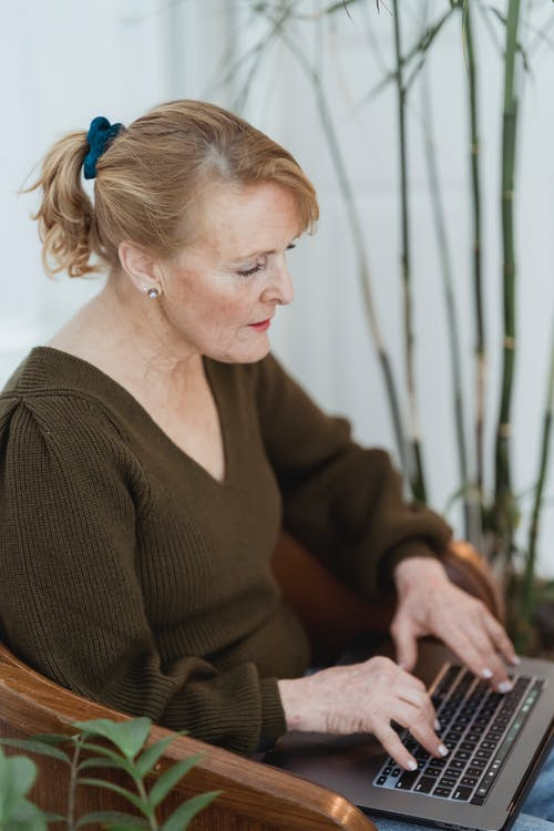 Serious mature female in casual outfit typing on modern netbook keyboard while sitting on comfy armchair in light living room