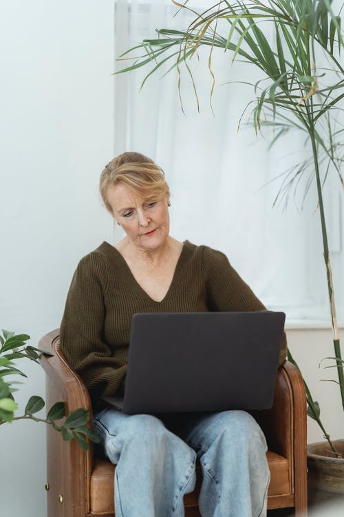 Thoughtful mature woman working on laptop in living room