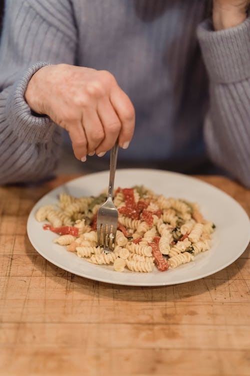 Crop unrecognizable woman eating fusilli pasta with tomatoes