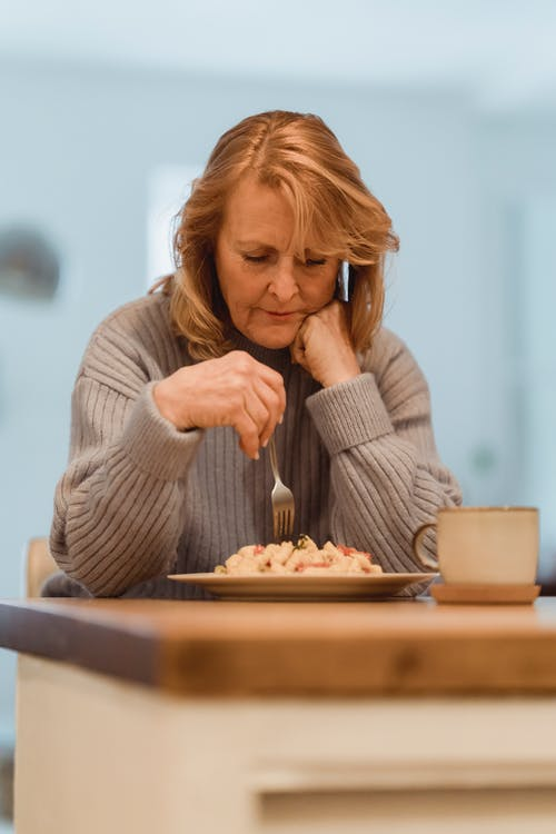 Focused mature woman eating freshly cooked pasta
