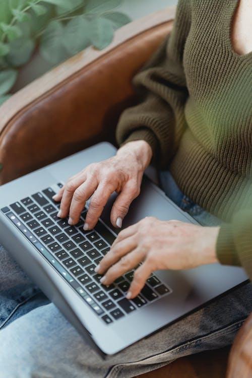 Crop faceless woman typing on laptop