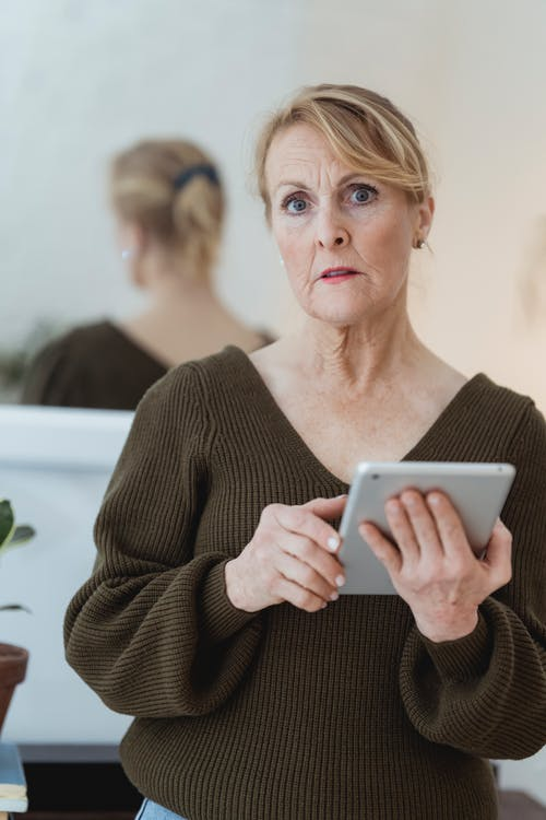 Pensive mature female in dark sweater using tablet and looking at camera while standing against mirror in light room