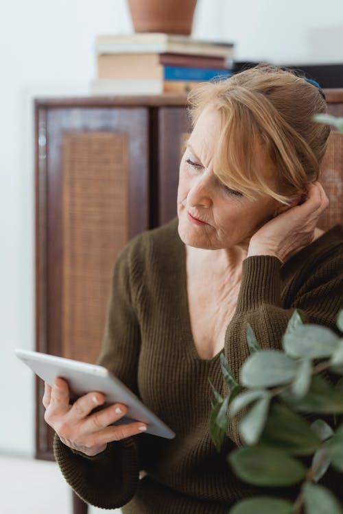 Concentrated mature female in casual sweater browsing contemporary tablet and touching head in contemplation in light room