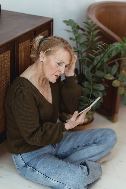 Pensive mature female touching hair while sitting with crossed legs on floor with cellphone at home