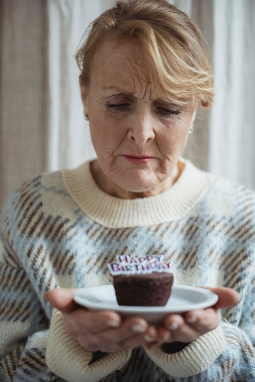 Upset woman with tasty muffin on birthday
