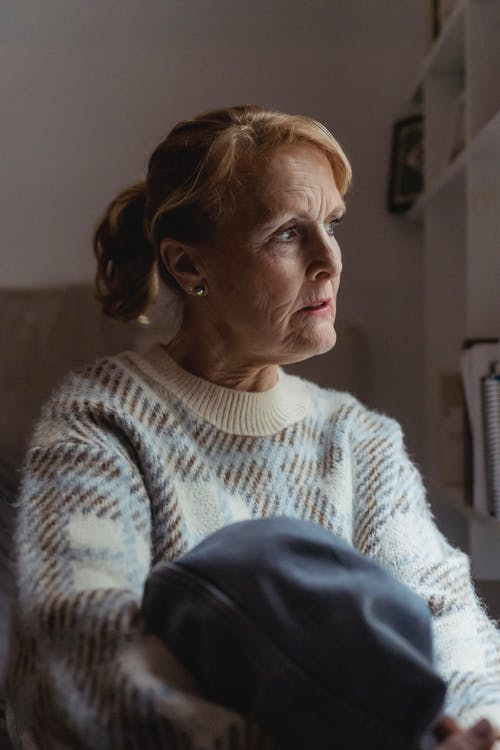 Wistful woman in sweater resting at home