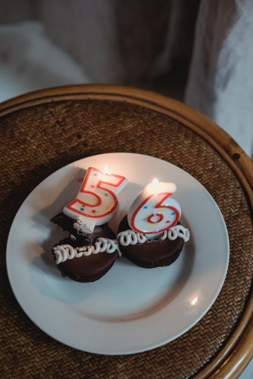 From above sweet chocolate birthday cupcakes decorated with burning candles in shape of numbers and placed on round table