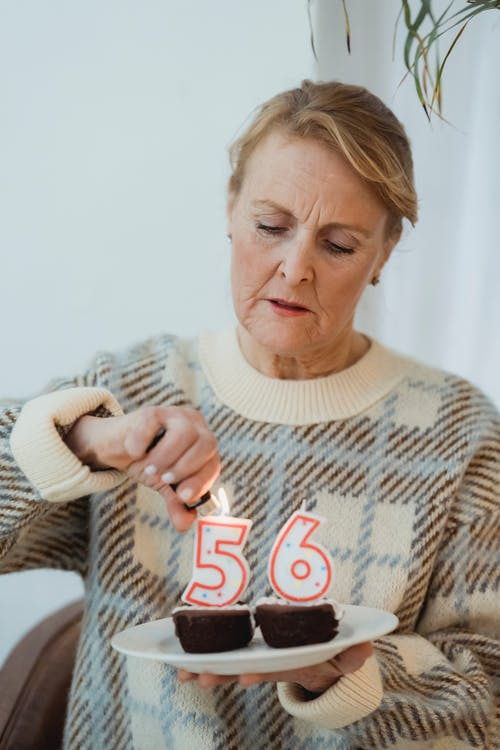 Senior female in casual sweater lightning candles in shape of numbers placed on birthday chocolate cupcakes