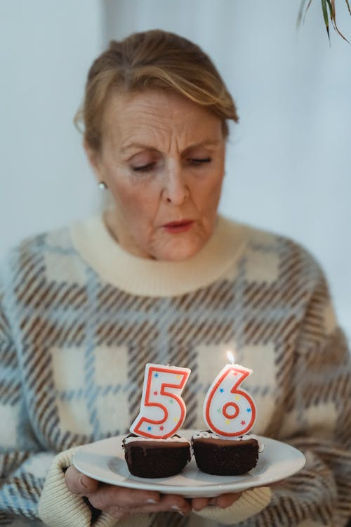 Mature woman blowing candles on birthday cupcakes