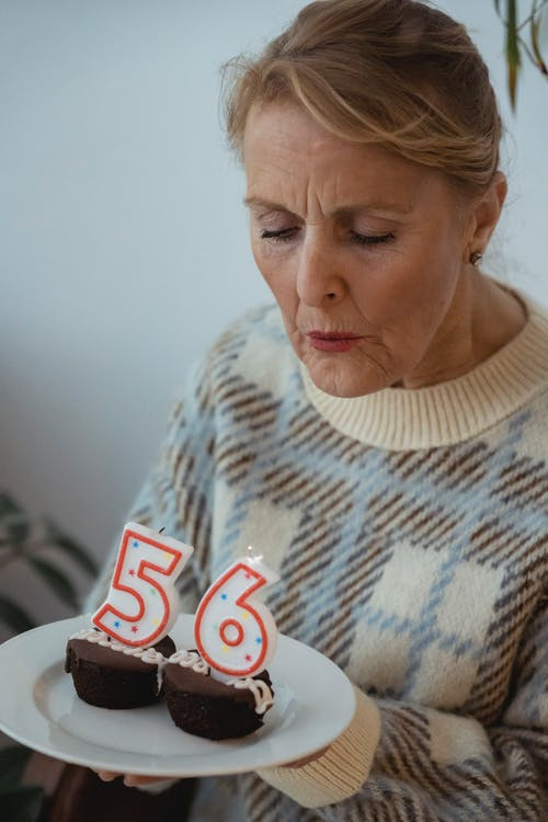 Crop senior female wearing sweater blowing candles on delicious cupcakes during birthday celebration
